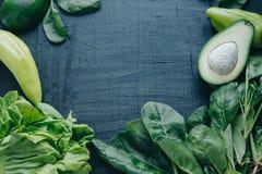 Opróżnia przestrzeń Świezi zieleni warzywa na czerni deski tle: zdjęcie stock