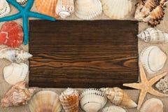 Opróżnia ramę ciemny drewno, seashells i rozgwiazda w piasku, Z przestrzenią dla twój teksta zdjęcie royalty free