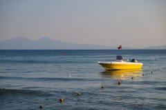 Opróżnia ratowniczą żółtą łódź z flagą Turcja morze na tle skalisty wybrzeże pod niebieskim niebem obrazy royalty free