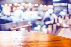 Opróżnia round drewna stół z plamy restauracyjnym tłem, egzamin próbny w górę f fotografia stock