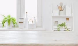 Opróżnia stołową deskę i defocused nowożytnego kuchni ściany tła pojęcie