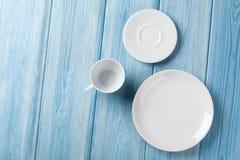 Opróżnia talerza i filiżanki na błękitnym drewnianym tle Zdjęcia Royalty Free