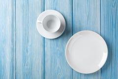 Opróżnia talerza i filiżanki na błękitnym drewnianym tle Obrazy Royalty Free