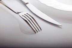 Opróżnia talerza z nożem i rozwidla na białym tle Zdjęcia Royalty Free