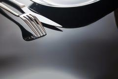 Opróżnia talerza z nożem i rozwidla na czarnym tle Obrazy Stock