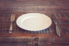 Opróżnia talerza z nożem i rozwidla na rocznika drewnianym stole Zdjęcia Stock