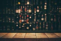 Opróżnia wierzchołek drewniany stół z zamazanym kontuaru barem, butelkami i obrazy stock