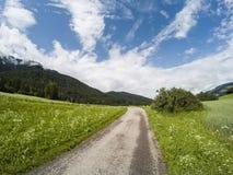 Opróżnia zmieloną drogę w Włochy Alps z górą i lasem na chmurnym niebie i tle dolomity obrazy royalty free