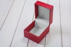 Opróżniam otwierał czerwona skóra zakrywającego prezenta pudełko na białym drewnianym stole Zdjęcia Royalty Free