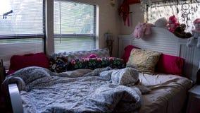 Opróżniam unmade girly młodej żeńskiej dziewczyny łóżkowego pokój z wiele personel zwierzętami w kolor menchiach z wiele poduszka zdjęcia royalty free