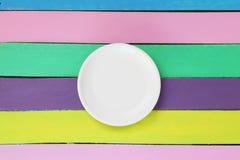 Opróżnia talerza na colourful drewnianym stole Obrazy Stock