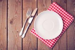 Opróżnia talerza na tablecloth na drewnianym stole na widok Zdjęcia Stock