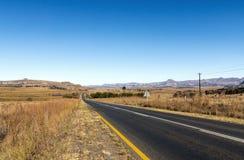 Opróżnia Wiejskiego Asfaltowej drogi bieg Przez Suchego zima krajobrazu Zdjęcia Stock