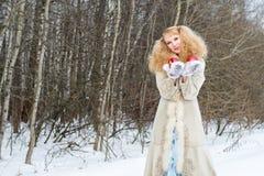 Oprecht glimlachende jonge vrouw in een de winterbos Stock Afbeeldingen