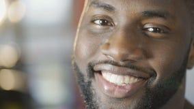 Oprechte vriendschappelijke glimlach op gezicht van de gelukkige Afrikaanse Amerikaanse mens die camera bekijken stock videobeelden