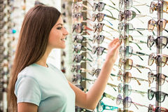 Oprician. Young woman at optician with glasses is looking for sunglasses Stock Photos