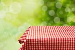 Opróżnia stół z czerwienią sprawdzał tablecloth nad zielonym bokeh tłem. Zdjęcia Stock