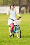 Oproepen me gebaar met mooi glimlachend wijfje op fiets stock afbeelding