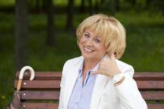 Oproepen me, Portret van mooie midden oude vrouw in het de zomerpark Royalty-vrije Stock Afbeeldingen