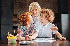 Opromieniona babcia obejmuje jej kreatywnie wnuków Zdjęcie Stock