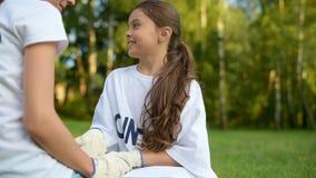 Opromieniony dziewczyny obsiadanie na trawie i opowiadać zgłaszać się na ochotnika zbiory