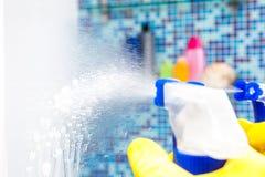 Opryskiwania cleaning fluid na łazienki lustrze podczas gdy domowi obowiązek domowy obraz stock