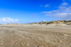 Opryskiwanie piasek podczas ciężkiej burzy na nagiej i pustej Holenderskiej Północnego morza plaży przy IJmuiderslag Zdjęcie Stock