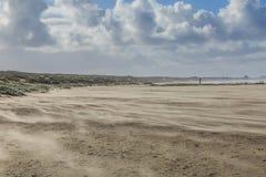 Opryskiwanie piasek podczas ciężkiej burzy na nagiej i pustej Holenderskiej Północnego morza plaży przy IJmuiderslag Obrazy Stock