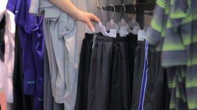 Opslag, kleren die op hangers hangen stock video