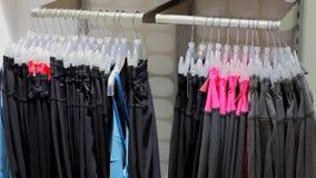 Opslag, kleren die op hangers hangen stock videobeelden