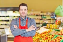 Opslagmanager met wapens in supermarkt worden gekruist die Stock Foto's