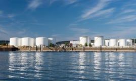 Opslagsilo's, brandstofdepot van aardolie en benzine op de banken van de rivier in West-Duitsland op een mooie blauwe hemel met w stock afbeelding