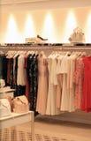 In opslagvertoning van women& x27; s kleren Stock Afbeelding