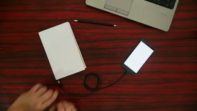 Optical character recognition video. Person connecting a book to a smartphone through an USB cable on a desk. Optical character recognition loading bar appearing stock video footage