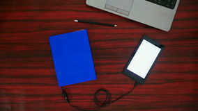 Optical character recognition video. Person connecting a book to a tablet through an USB cable on a desk. Optical character recognition software displaying the stock video footage