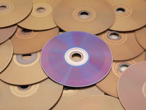 Optical Disc Contrast. Purple disc on bronze discs royalty free stock photos