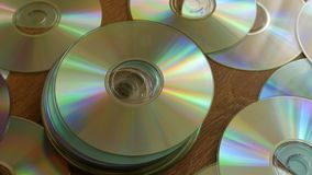 Optical Discs falling onto pile of DVDs or CDs. stock footage