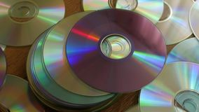Optical Discs falling onto pile of DVDs or CDs. stock video