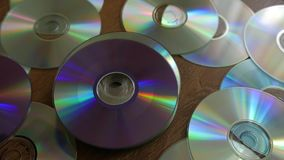 Optical Discs falling onto pile of DVDs or CDs. stock video footage