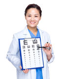 Optical doctor with eye chart and glasses Royalty Free Stock Photography