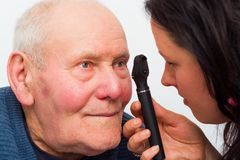 Optical Exam. Optician checking elderly patient's cataracts with optical device Royalty Free Stock Photo