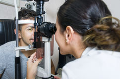 Optical exam to young man, professional woman. Young boy in an optical scans machine exams his vision and optometry Stock Image