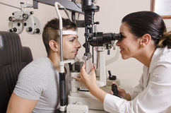 Optical exam to young man, professional woman. Woman in optical dark lab doing eyes exam for glasses graduation Stock Photos