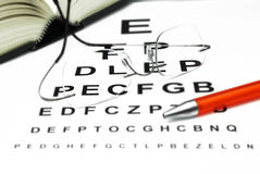 Optical eye test. Optician with eye test and book Royalty Free Stock Photo