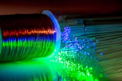 Optical fiber flexible transparent glowing blue and green agains a cooper wire coil stock photos
