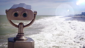Optical flares footage of a tourist telescope at the seaside with rough waves stock video footage