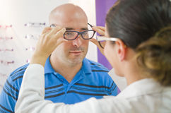 Optical glasses test on man. Prfessional optometrist woman Royalty Free Stock Images