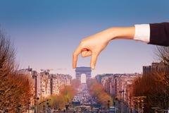 Optical illusion of hand holding Arc de Triumph