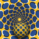 Optical illusion illustration. A ball is moving in yellow blue polka dots rotating hole. Stock Photo