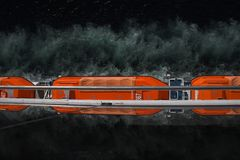 Optical illusion of orange life boats on a ship. Optical illusion of life boats on a ship. The top of the photo is the actual boat. The bottom of the photo is royalty free stock images